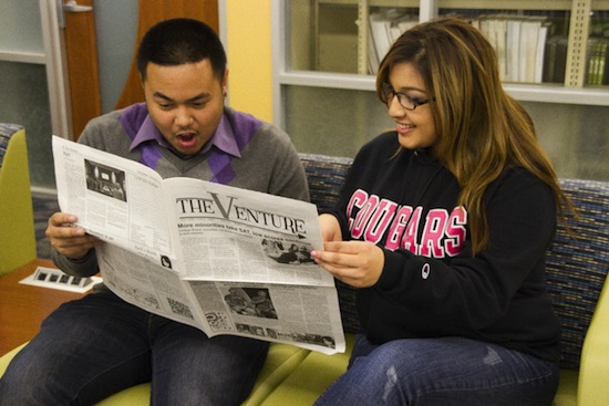 hispanic college students reading a newspaper